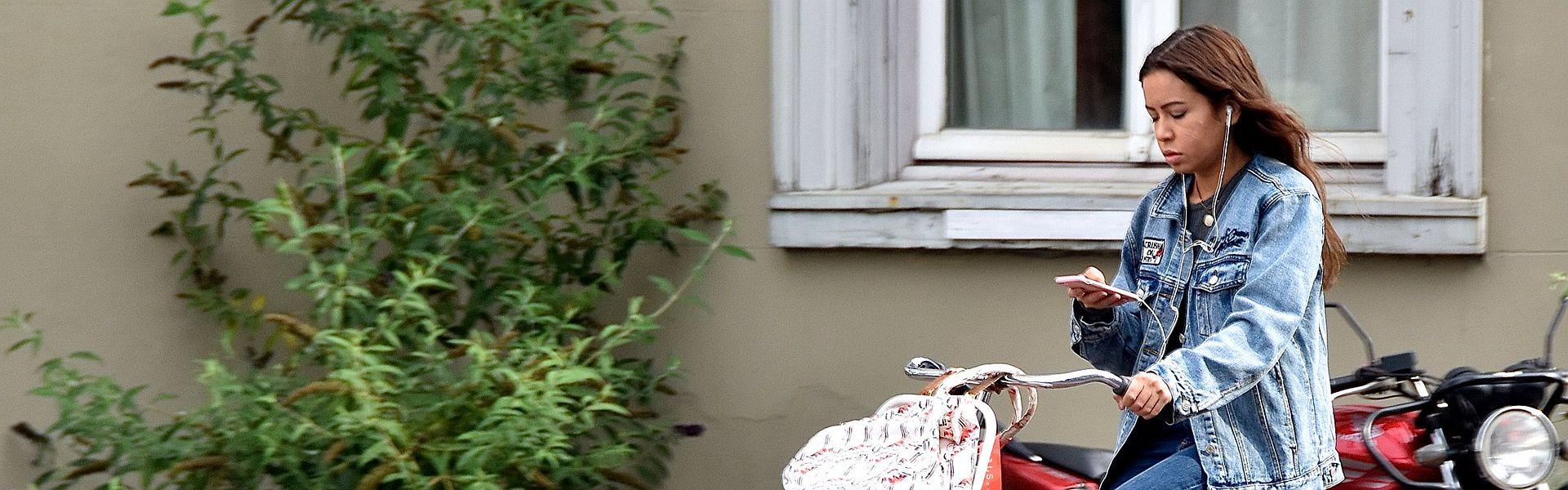 Onoplettend meisje append op de fiets bij de column 'Onoplettend' van Paul de Vries Schrijft. Foto 'Texting Elvis' door FaceMePLS